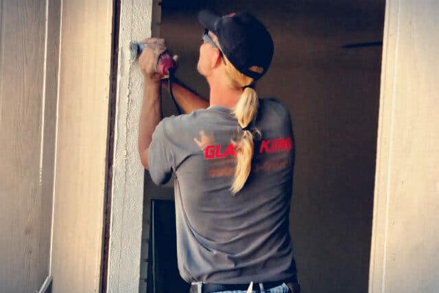 A Glass King tech is working on replacing a broken window. Glass King offers the best in home window repair.