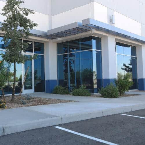 A nice looking, modern office building in a Chandler AZ office park. The office exterior is white with modern lights hanging on top, with blue accent trim beneath. The photo focuses on newly installed windows from commercial glass services provider Glass King.